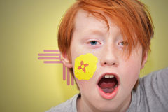 Redhead fan boy with new mexico state flag painted on his face. Royalty Free Stock Image