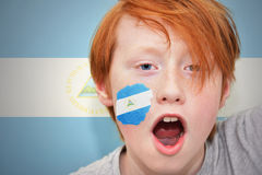 Redhead fan boy with nicaraguan flag painted on his face. On the nicaraguan  flag background Royalty Free Stock Images