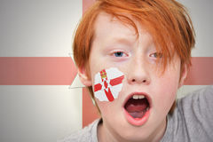 Redhead fan boy with northern ireland flag painted on his face. On the northern ireland flag background royalty free stock photography