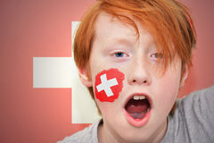 Redhead fan boy with swiss flag painted on his face Royalty Free Stock Photo