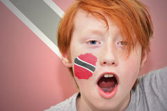 Redhead fan boy with trinidad and tobago flag painted on his face Stock Image