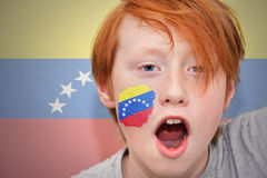 Redhead fan boy with venezuelan flag painted on his face. On the venezuelan  flag background Stock Images