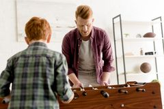 Redhead father and son playing table football together at home royalty free stock photos