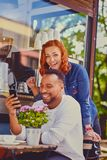 Redhead female and Black smiles male using smartphone. stock photos