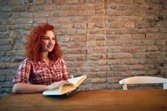 Redhead female with book stock photos