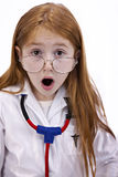 Redhead female child. Beautiful little seven year old redhaired girl with big brown eyes, doctor's labcoat; large glasses and stethoscope with a look of surprise Royalty Free Stock Image