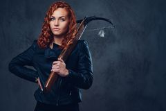 Redhead female  holds crossbow. Redhead female dressed in an elegant suit holds crossbow Stock Photo