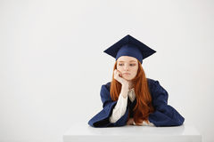 Redhead female graduate in mantle thinking sitting over white background. Copy space. Beautiful redhead female graduate in mantle thinking sitting over white Royalty Free Stock Photo