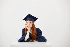 Redhead female graduate in mantle thinking sitting over white background. Copy space. Beautiful redhead female graduate in mantle thinking sitting over white Royalty Free Stock Images