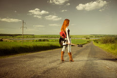 Redhead female guitarist at rural freeway Stock Photos