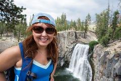 Redhead female hiker wearing a ballcap poses at Rainbow Falls in California along the John Muir Trail stock photos