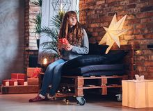 A woman holds a Christmas gift in a living room with loft interior. Royalty Free Stock Photos
