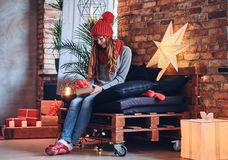 A woman holds a Christmas gift in a living room with loft interi Stock Photography