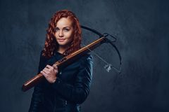 Redhead female  holds crossbow. Redhead female dressed in an elegant suit holds crossbow Stock Images