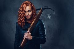 Redhead female  holds crossbow. Redhead female dressed in an elegant suit holds crossbow Stock Photography