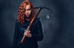 Redhead female  holds crossbow. Royalty Free Stock Photos