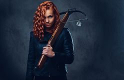 Redhead female  holds crossbow. Royalty Free Stock Image