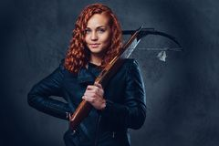 Redhead female  holds crossbow. Redhead female dressed in an elegant suit holds crossbow Royalty Free Stock Photo