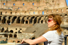 The redhead female tourist looks at the Colosseum in Rome Stock Images