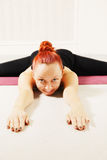 Redhead on floor legs stretched closeup Royalty Free Stock Image