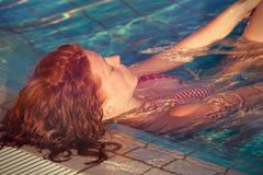 Redhead freckled young woman in pool real people concept. Redhead freckled young woman in pool enjoy in warm sun lean on pool edge  real people concept Royalty Free Stock Images