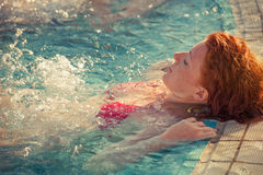 Redhead freckled young woman in pool real people concept. Redhead freckled young woman in pool enjoy in warm sun lean on pool edge  real people concept Stock Images
