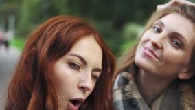 Redhead friends taking selfie with a smart phone and making faces and fun. Redhead Friends taking selfie with a smart phone and making faces and fun stock footage