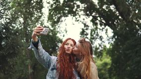Redhead friends taking selfie with a smart phone and making faces and fun stock footage