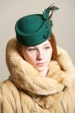 Redhead in fur coat and green hat Stock Images