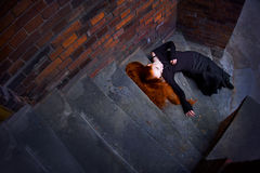 Redhead girl. Gothic girl lying on stairway Royalty Free Stock Image