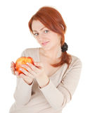 Redhead girl with apple. Focus on apple Royalty Free Stock Image