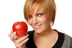 Redhead girl with apple. Redhead girl with red apple, focus on apple Royalty Free Stock Photo