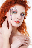 Redhead girl with art makeup. Portrait of redhead girl with art makeup and painted butterfly Royalty Free Stock Photos