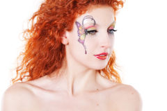 Redhead girl with art makeup. Portrait of redhead girl with art makeup and painted butterfly Royalty Free Stock Images