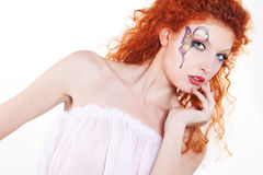 Redhead girl with art makeup. Portrait of redhead girl with art makeup and painted butterfly Royalty Free Stock Photo