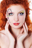 Redhead girl with art makeup. Portrait of redhead girl with art makeup and painted butterfly Stock Images