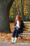 Redhead girl in autumn city park read paper sheet, sit on wood bench, one people at day, yellow leaves fall Royalty Free Stock Photos