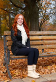Redhead girl in autumn city park, sit on wood bench, one people. At day, yellow leaves fall Stock Photos