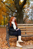Redhead girl in autumn city park, sit on wood bench, one people. At day, yellow leaves fall Royalty Free Stock Photography