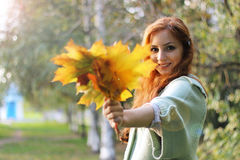 Redhead girl Autumn leaves. Pretty young woman posing on camera in autumn park royalty free stock image