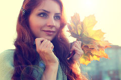 Redhead girl Autumn leaves. Pretty young woman posing on camera in autumn park royalty free stock photos