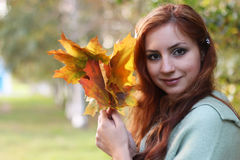 Redhead girl Autumn leaves. Pretty young woman posing on camera in autumn park stock photography