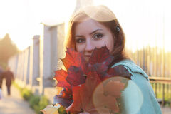 Redhead girl Autumn leaves. Pretty young woman posing on camera in autumn park royalty free stock images