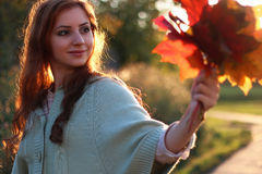 Redhead girl Autumn leaves. Pretty young woman posing on camera in autumn park royalty free stock photo