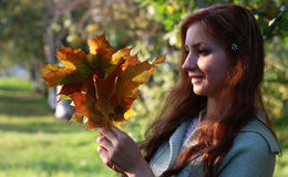 Redhead girl Autumn leaves. Pretty young woman posing on camera in autumn park royalty free stock photography