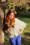 Redhead girl Autumn leaves. Pretty young woman posing on camera in autumn park stock photo