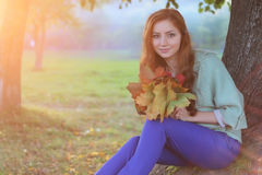 Redhead girl Autumn leaves. Pretty young woman posing on camera in autumn park stock image