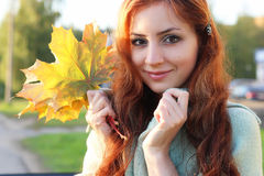 Redhead girl Autumn leaves. Pretty young woman posing on camera in autumn park stock photos