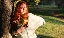 Redhead girl Autumn leaves. Pretty young woman posing on camera in autumn park stock images