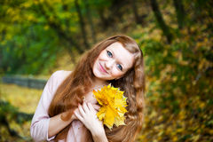 Redhead girl in autumn park Royalty Free Stock Photo